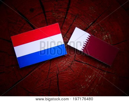 Dutch Flag With Qatari Flag On A Tree Stump Isolated