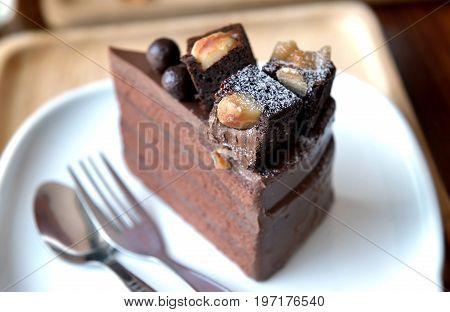 Chocolate Cake On Dish At Coffeeshop Table