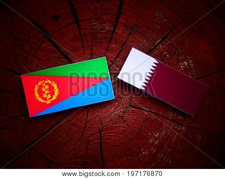 Eritrean Flag With Qatari Flag On A Tree Stump Isolated