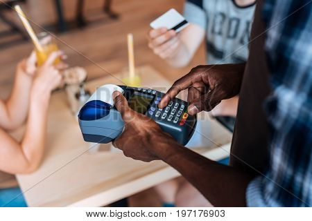 Cropped View Of African American Waiter With Terminal Taking Payment With Credit Card In Cafe