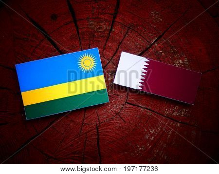 Rwanda Flag With Qatari Flag On A Tree Stump Isolated