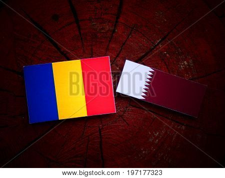 Chad Flag With Qatari Flag On A Tree Stump Isolated