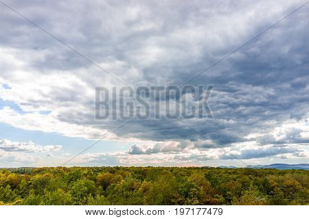 Stormy Large Gray Cloudscape With Green Forest During Autumn
