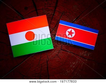 Niger Flag With North Korean Flag On A Tree Stump Isolated