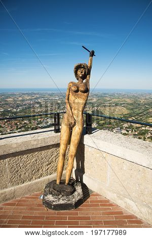 San Marino Republic San Marino - June 18th 2017: view of the wooden sculpture of nude woman in historic center in sunny day against beautiful view of valley blue sea and sky in San Marino city