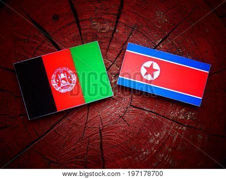 Afghani Flag With North Korean Flag On A Tree Stump Isolated