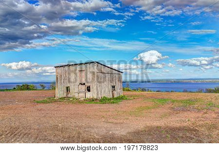 Old Vintage Slanted Shed In Summer Landscape Brown Soil Field In Countryside