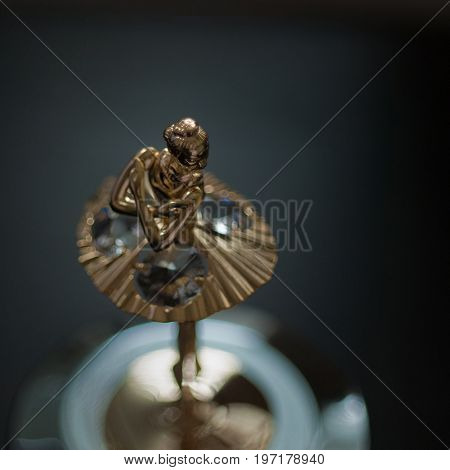 Top view of ballerina statuette on music box. Dark photo grain aded.