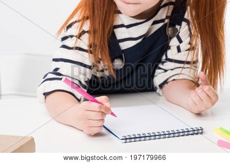 Cropped Shot Of Schoolgirl Holding Felt Tip Pen And Drawing In Notebook