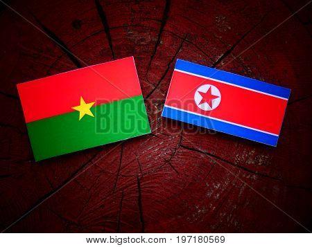 Burkina Faso Flag With North Korean Flag On A Tree Stump Isolated