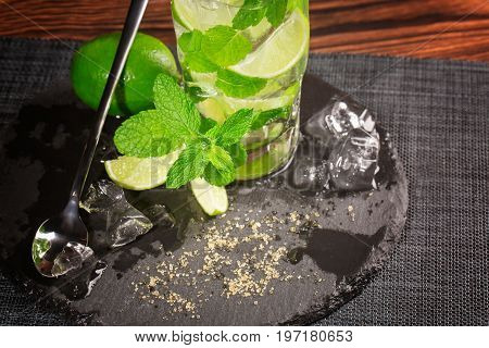 Summer colourful beverage with fresh lime segments, whole lime ice cubes and leaves of peppermint on a black napkin. A transparent highball glass with a long tea-spoon on the wooden table.