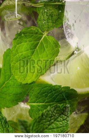 A tasty organic beverage with fresh lime segments, ice and leaves of mint. Summer beverage close-up as a texture. Summer refreshing beverages for parties. Vegetarian drink.