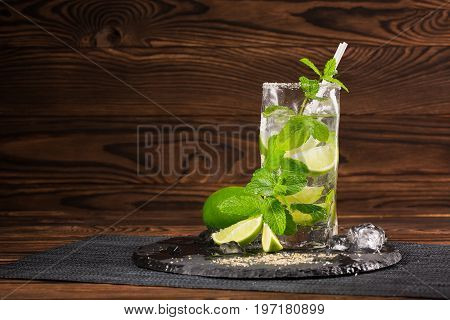 Close-up of a tasty organic beverage with fresh slices of lime, straw, ice cubes and leaves of peppermint on a black tablecloth on a wooden background. Summer beverages.