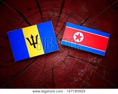 Barbados Flag With North Korean Flag On A Tree Stump Isolated