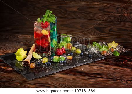 Bright blue and red beverages on a black table-napkin. Beautiful bright cocktails with mint, slices of lime, berries, ice and carambola in transparent highball glasses on the wooden background.
