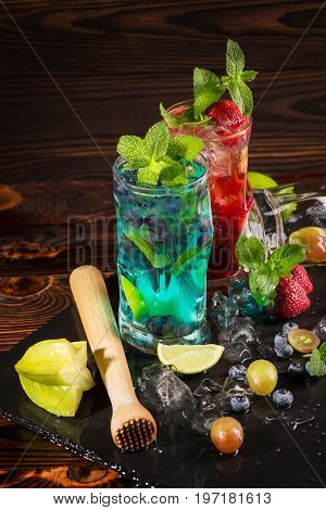 Close-up of blue and red beverages on a black table-napkin. Refreshing bright cocktails with mint, berries, ice and carambola in transparent highball glasses on the wooden background.