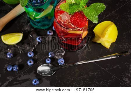 Top view picture of blue and red beverages on a black background. Refreshing bright cocktails with mint, slices of lime and lemon, berries, ice and carambola in transparent highball glasses.