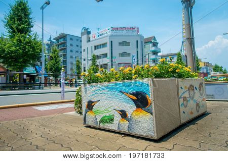 OSAKA, JAPAN - JULY 18, 2017: Close up a stoned flowerpot with some yellow flowers over it and a beautiful draw of a sea animals in the flowerpot in Dowtown view of Osaka cityscape in summer season at Osaka, Japan.