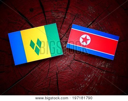Saint Vincent And The Grenadines Flag With North Korean Flag On A Tree Stump Isolated