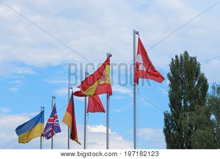 a group of european country flags waving on flag poles against blue sky. flags of Ukraine Great Britain Germany Spain Switzerland. with copy space