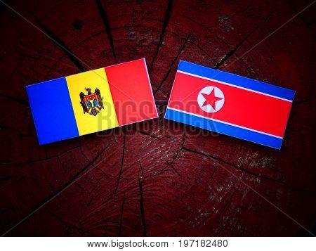 Moldovan Flag With North Korean Flag On A Tree Stump Isolated