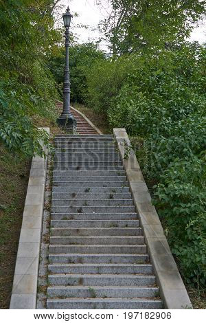 granite stairs on green hills with lantern in a park. footpath upstairs