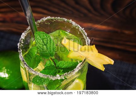 Bright natural beverage with fresh lime and lemon segments, carambola and leaves of mint. Bright cocktail in a transparent highball glass with a lond tea-spoon isolated on the wooden background.