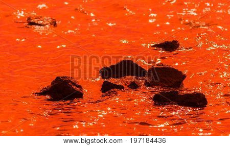Black stones in deep orange water. Reflections of light on the water.