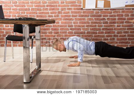 Attractive Happy Businessman Doing Push Up In Modern Office