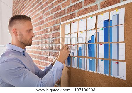Close-up Of A Businessman Arranging Graph Made On Notes Over The Corkboard