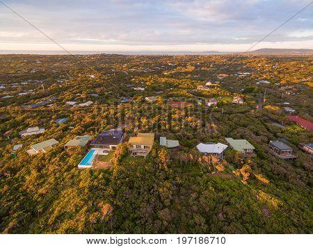 Aerial view of luxury homes among lush coastal vegetation in Rye suburb at sunset. Melbourne Australia
