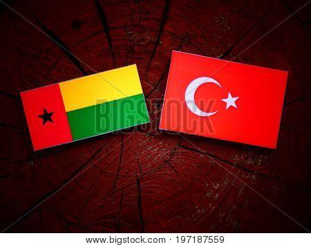 Guinea Bissau Flag With Turkish Flag On A Tree Stump Isolated