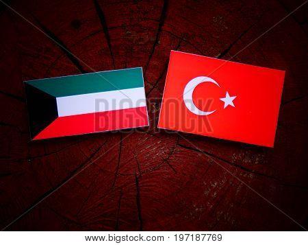 Kuwaiti Flag With Turkish Flag On A Tree Stump Isolated