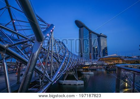 SINGAPORE - JUNE 17 2014 : Concrete covered with stainless bridge to Marina Bay Sands Hotel during twilight time in Singapore