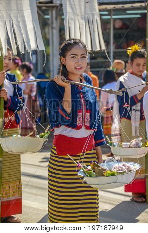 CHIANGMAI THAILAND - JANUARY 25 2015: Indigenous girl holding counterpoise enameled basin of food in parade of 22nd Traditional Skirt Fabric and The Indigenous Product and Culture Festival in Mae Chaem Chiangmai Thailand