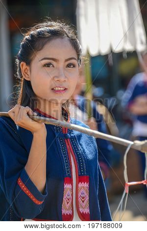 CHIANGMAI THAILAND - JANUARY 25 2015: Indigenous girl holding counterpoise with 2 enameled basin of food in parade of 22nd Traditional Skirt Fabric and The Indigenous Product and Culture Festival in Mae Chaem Chiangmai Thailand