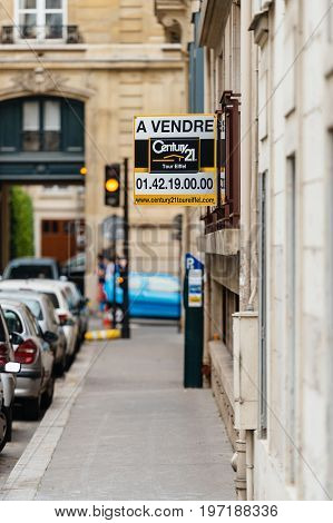 PARIS FRANCE - MAY 21 2016: Century 21 for sale a vendre signage on the corner of a building in Paris France. Century 21 Real Estate LLC is an American real estate agent franchise company founded in 1971