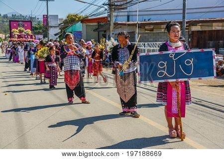 CHIANGMAI THAILAND - JANUARY 25 2015: Hill Tribe people with traditional costume holding board of Hmong nationality name in parade of 22nd Traditional Skirt Fabric and The Indigenous Product and Culture Festival in Mae Chaem Chiangmai Thailand