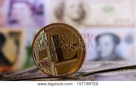Golden Litecoin agaisnt of different banknotes on background. Cryptocurrency Trading concept .