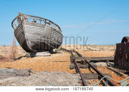 Old wooden fishing boat falling to pieces on a beach