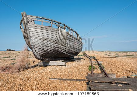Rotting wooden fishing boat and nets on a beach