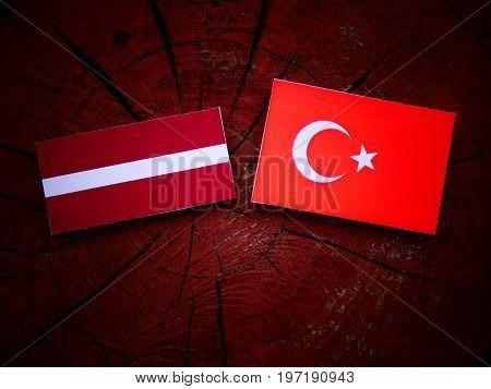 Latvian Flag With Turkish Flag On A Tree Stump Isolated