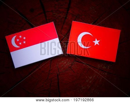 Singaporean Flag With Turkish Flag On A Tree Stump Isolated