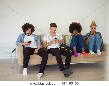 multiethnic group of young people sitting on a sofa at home, staring at smartphone, being antisocial, smartphone addiction