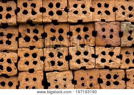 Close up abstract background of red clay block for wall construction. Texture of clay brick wall design with holes.