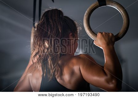 Woman Athlete Exercising On Gymnastic Rings, Black Background, Indoors
