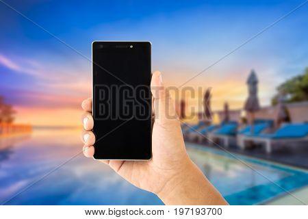 hand using smartphone with view sunrise of hotel swimingpool