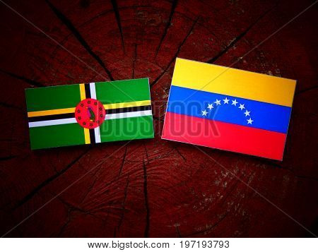 Dominica Flag With Venezuelan Flag On A Tree Stump Isolated