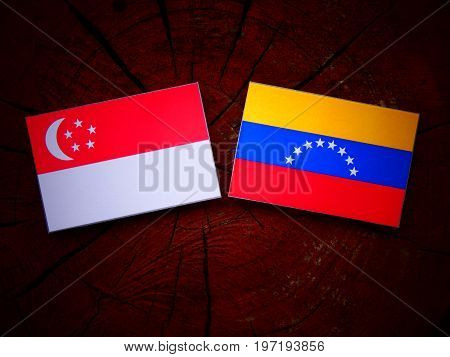Singaporean Flag With Venezuelan Flag On A Tree Stump Isolated