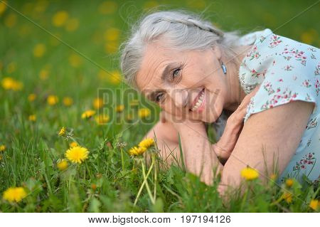 Beautiful senior woman lying on meadow with dandelions